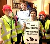 young volunteers holding amphibian crossing signs