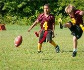 boys kicking a football during flag football game