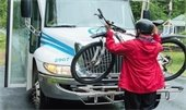 photo of person loading bicycle on advance transit bus