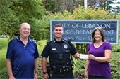 Valerie Thompson and Dave Brooker present donation to officer