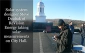 Solar system designer Steve Dzubak of ReVision Energy taking solar measurements on City Hall roof.
