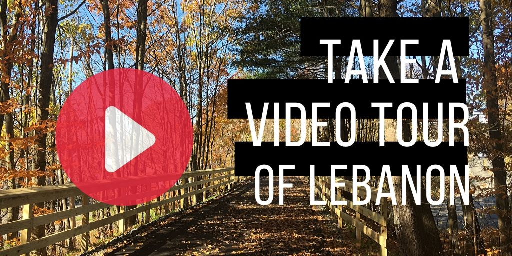 photo of rail trail covered in fall leaves with video play button