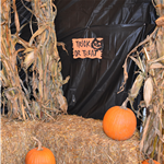 Halloween trick-or-treating display with hay bales and pumpkins