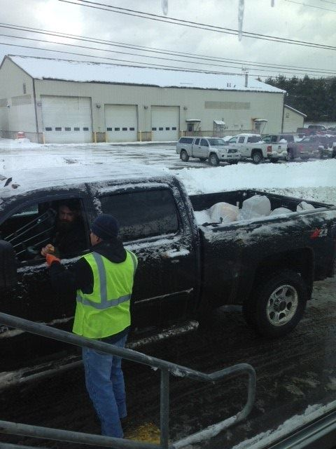 Staff member receiving landfill ticket from local patron at the Solid Waste Facility during winter