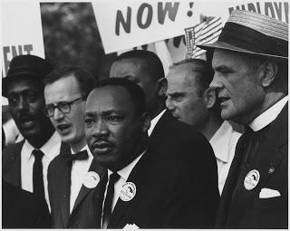 Black and white photo of Martin Luther King Jr. standing in a crowd of people holding signs