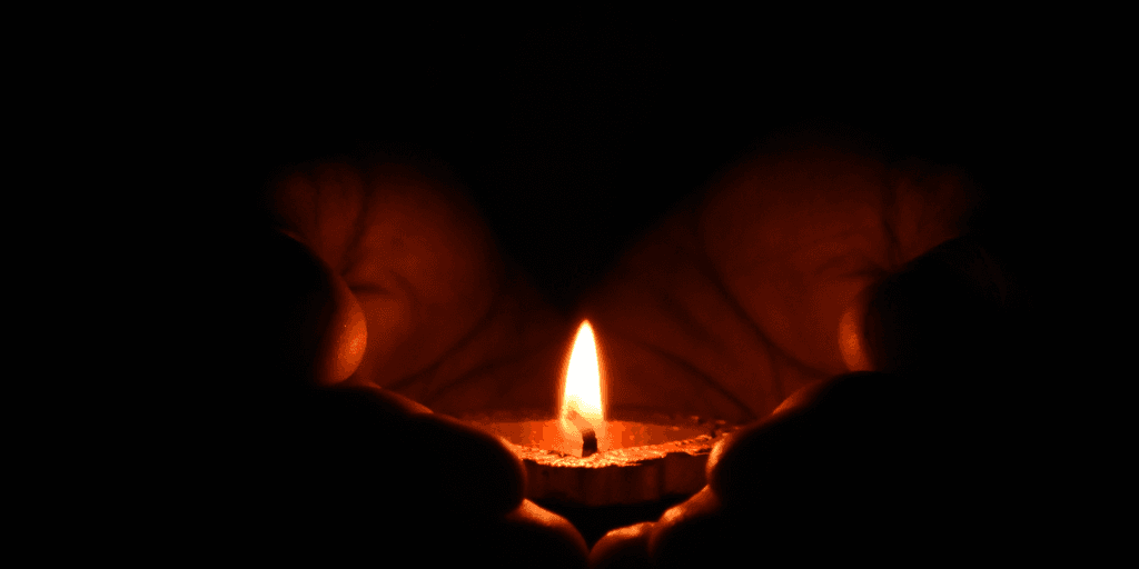 Hands holding lit candle