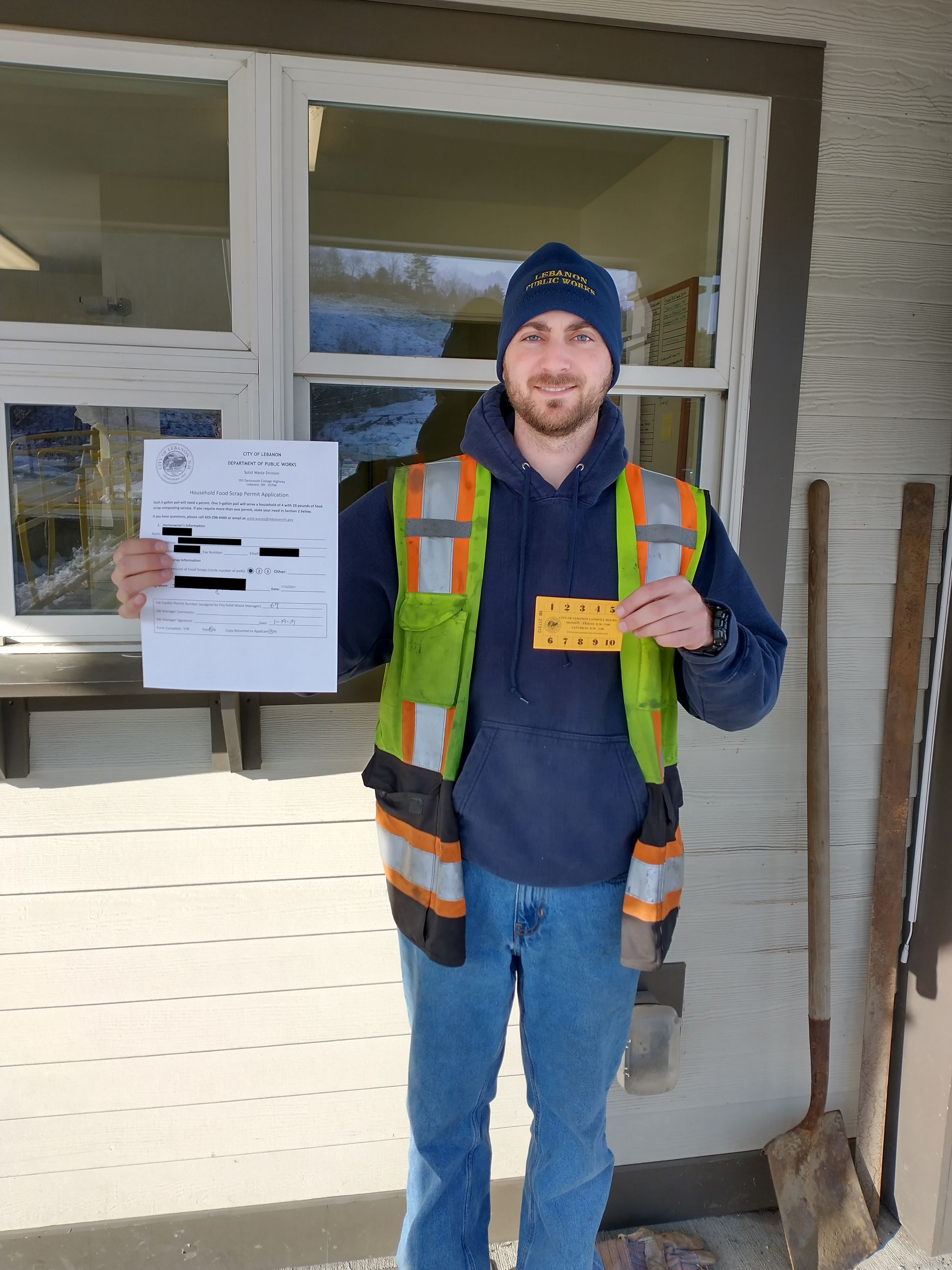 Photo of solid waste attendant holding permit and punch card Opens in new window