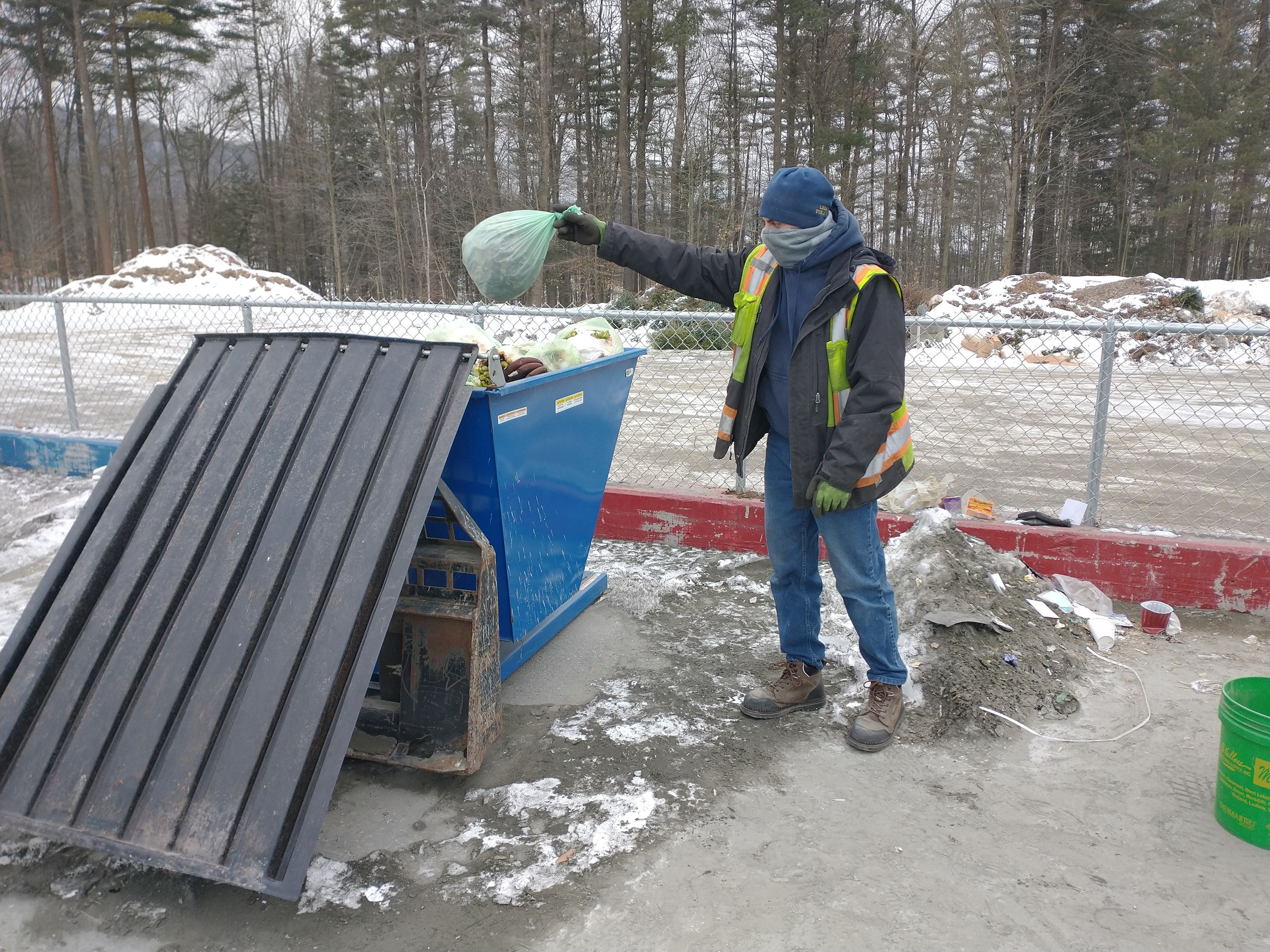 photo of solid waste attendant throwing away food scraps bag Opens in new window