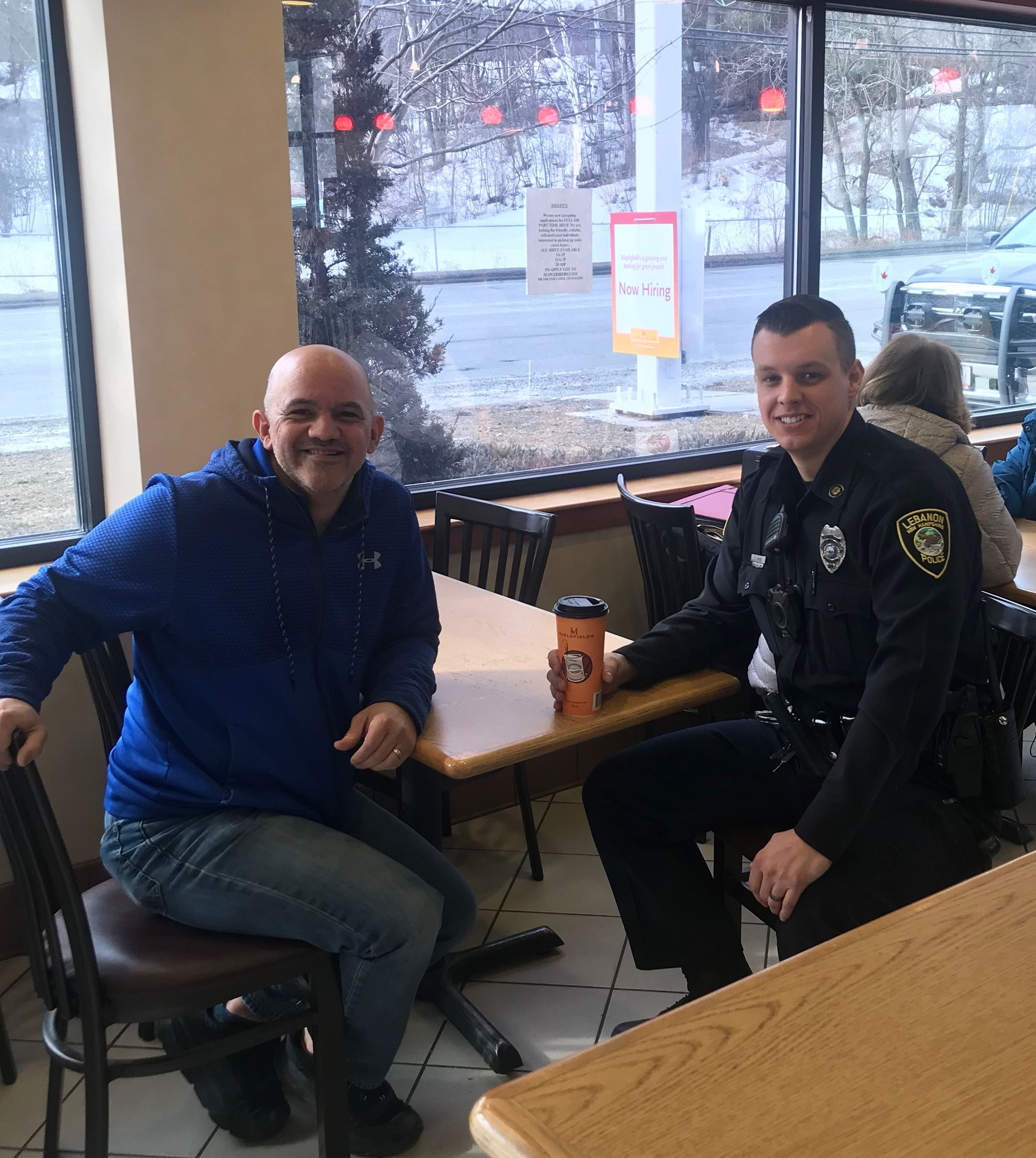 Officer Payne sitting with citizen at Coffee with a Cop