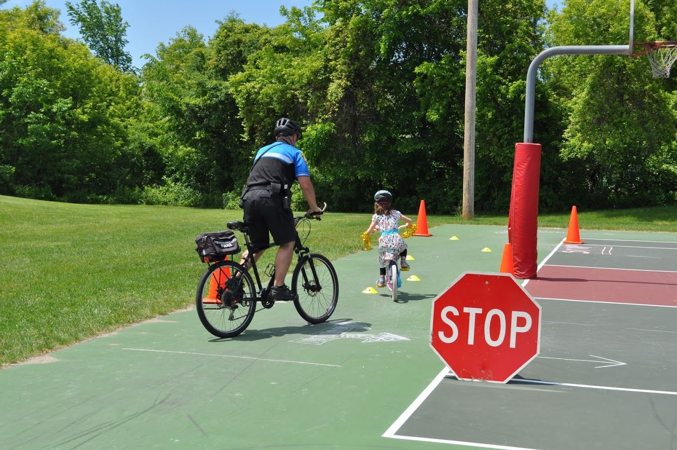 Officer and Child Biking Through Course